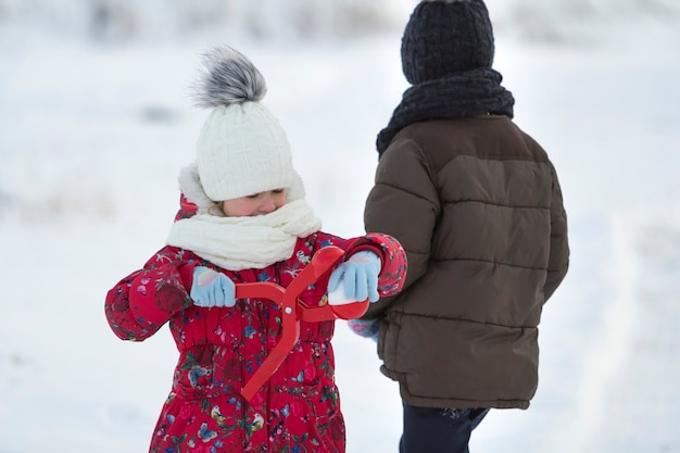 Two cute young children in warm clothing with bright snow clips playing having fun making snowballs on winter cold day on white bright blurred copy space background. outdoors activity, holiday games.
