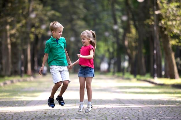 Два милых молодых забавных улыбающихся ребенка, девочка и мальчик, брат и сестра, прыгающие и весело проводящие время на стертом ярком солнечном переулке зеленые деревья bokeh. концепция счастливого беззаботного детства.