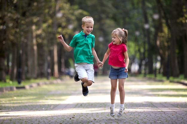 Две милые молодые смешные улыбающиеся дети, девочка и мальчик, брат и сестра, прыгать и веселиться на затуманенное яркий солнечный парк.