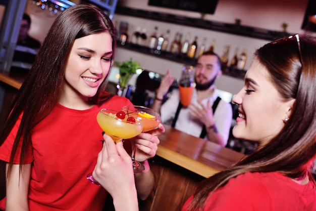 2人のかわいい若いガールフレンドの女の子がナイトクラブやバーでカクテルを飲んで、楽しんで、話している