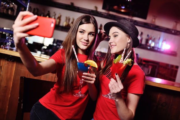 Two cute young girlfriends drink cocktails and are photographed