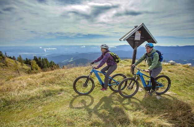 美しい環境の山の頂上にいる2人のサイクリスト