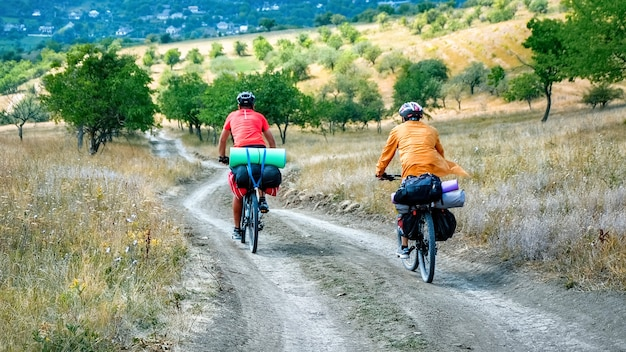 Two cyclists in helmets with bicycles full of traveler's stuff moving on the country road through rare green trees