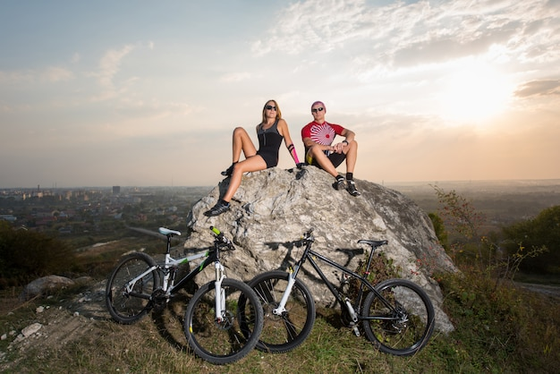 Two cyclists man and woman sitting on a stone near bicycles at sunset