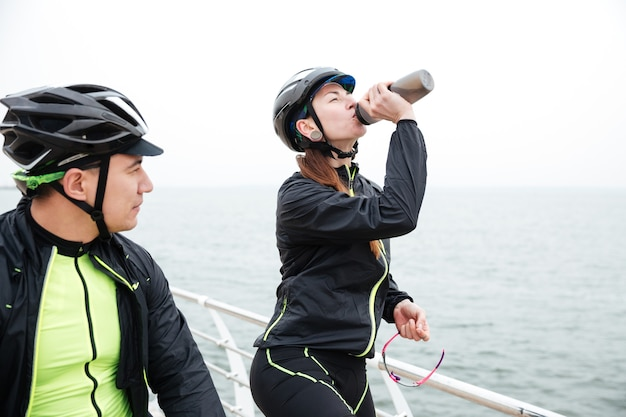 Two cyclists resting near sea. woman drinking water and man looking at sea