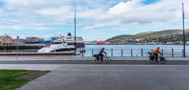 Two cyclists on waterfront on a background of a panorama of hammerfest, norway