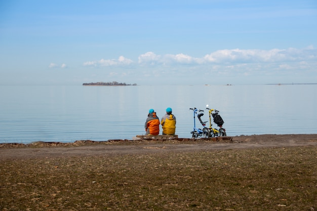 Two cyclists with bicycles relaxing on coast and enjoying view of sea