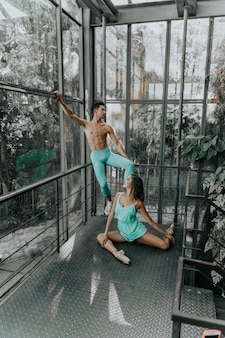 Two dancers in the interior of a greenhouse