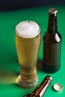 2つの暗いビール瓶、ビールのグラスと緑と青の背景に泡。