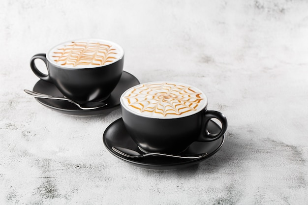 Two dark cups of coffee with milk caramel latte art texture isolated on bright marble background. overhead view, copy space. advertising for cafe menu. coffee shop menu. horizontal photo.