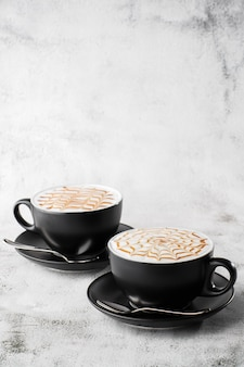 Two dark cups of coffee with milk caramel latte art texture isolated on bright marble background. overhead view, copy space. advertising for cafe menu. coffee shop menu. vertical photo.