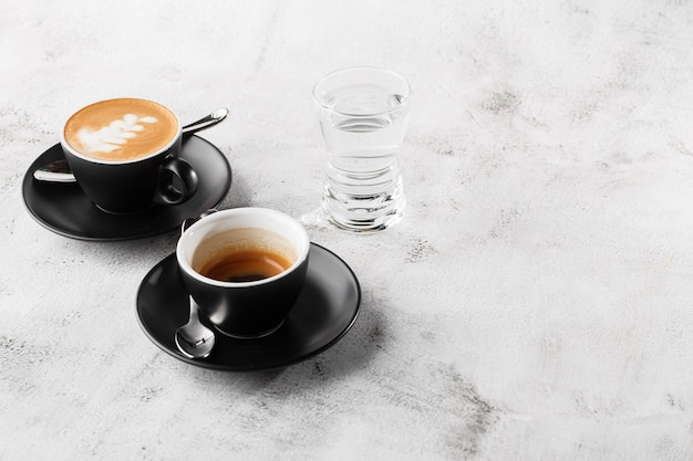 Two dark cups of hot black coffee, espresso, cappuccino with milk isolated on bright marble background. overhead view, copy space. advertising for cafe menu. coffee shop menu. horizontal photo.