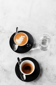Two dark cups of hot black coffee, espresso, cappuccino with milk isolated on bright marble background. overhead view, copy space. advertising for cafe menu. coffee shop menu. vertical photo.
