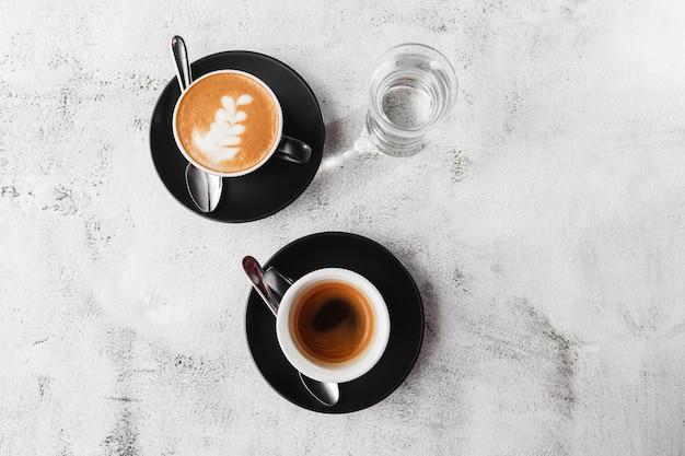 明るい大理石の背景に分離された牛乳とホットブラックコーヒー、エスプレッソ、カプチーノの2つの暗いカップ。俯瞰、コピースペース。カフェメニューの宣伝。コーヒーショップメニュー。横の写真。