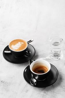明るい大理石の背景に分離された牛乳とホットブラックコーヒー、エスプレッソ、カプチーノの2つの暗いカップ。俯瞰、コピースペース。カフェメニューの宣伝。コーヒーショップメニュー。縦の写真。
