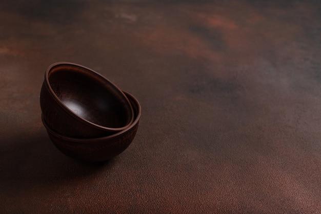 Две темные глиняные миски ручной работы на коричневом столе