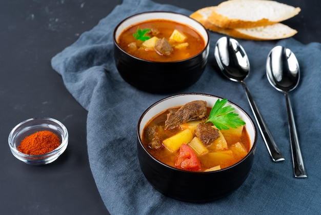 Two dark plates with hungarian goulash soup on a dark linen napkin. horizontal orientation. side view high quality photo