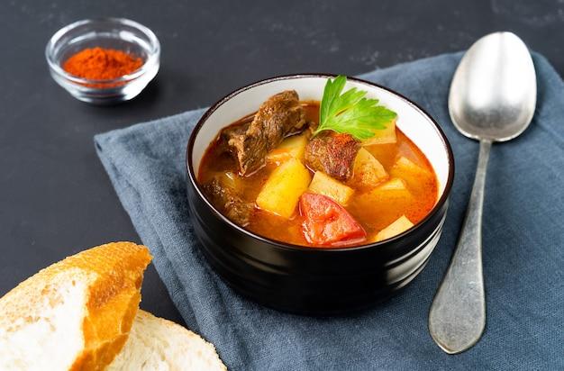 어두운 리넨 냅킨에 헝가리 굴 라시 수프와 함께 두 개의 어두운 접시. 수평 방향. 측면보기. 고품질 사진