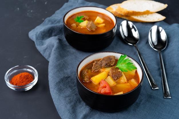 Две темные тарелки с венгерским супом-гуляшем на темной льняной салфетке. горизонтальная ориентация. вид сбоку фото высокого качества
