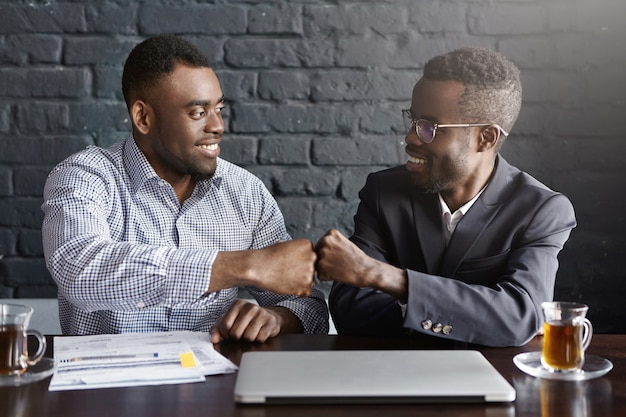 Two dark-skinned businesspeople in formal wear giving each other fist bump