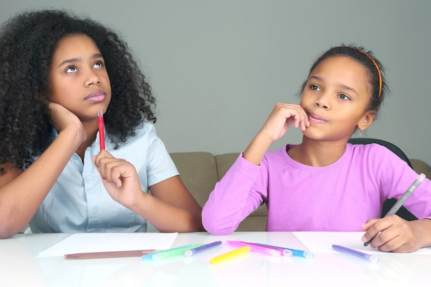 Two dark-skinned girls dream about the idea of drawing. creativity drawing in childhood