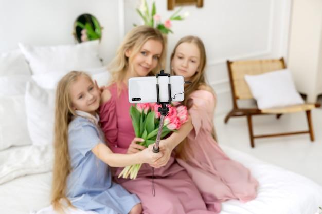 Две дочери и мама делают селфи на телефон