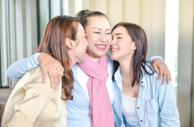 Two daughters embracing fragrant mother with love