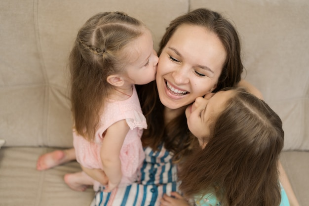 Two daughters kissing their mommy