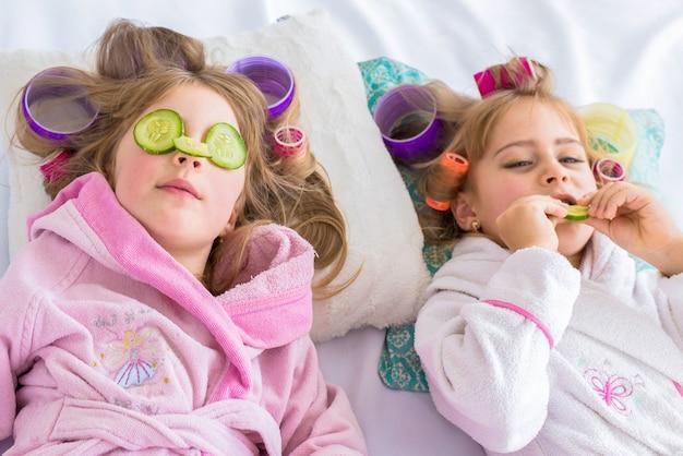 寝室のベッドに横たわっている髪のカーラーと目のキュウリを持つ2人の娘は家にいます