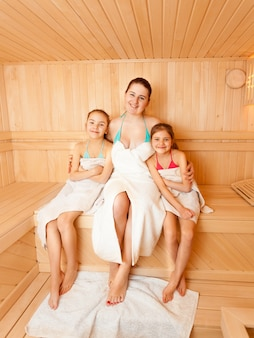 Two daughters with mother sitting on bench at sauna