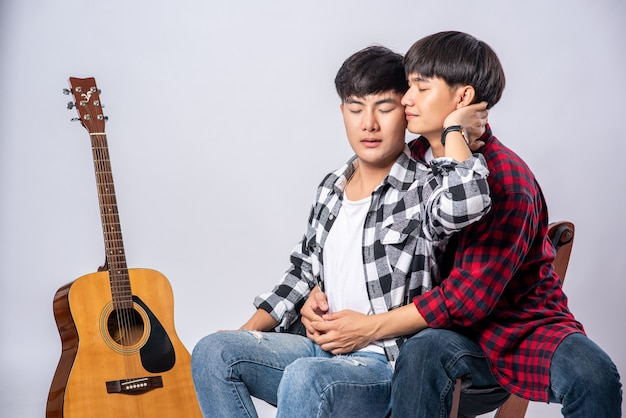 Two dear young men were sitting, cuddling in a chair, and with a guitar beside.