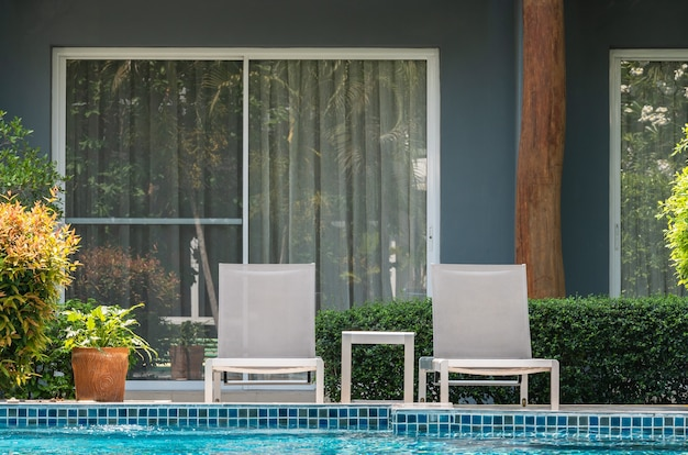 Two deck chairs and table beside outdoor swimming pool in resort hotel for vacation travel leisure