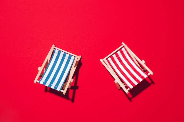 Two deck chairs with hard shadow on red paper background.