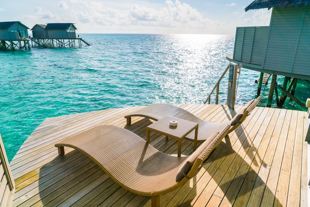 Two deck chairs on the wooden floor in water villa sunset time ,maldives island