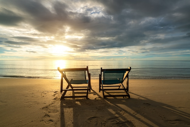 Two deckchairs on the beach at sunset with a tropical sea
