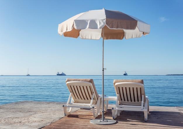 Two deckchairs under a parasol near the calm sea