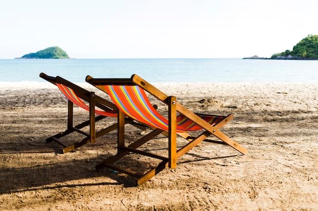 Two deckchairs on sandy beach