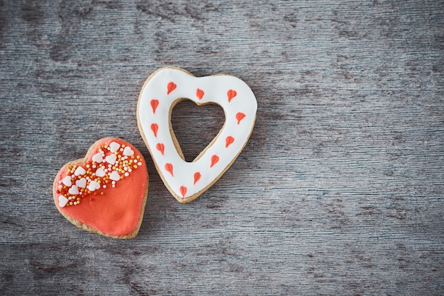 Two decorated heart shape cookies on gray background with copy space. valentines day food concept