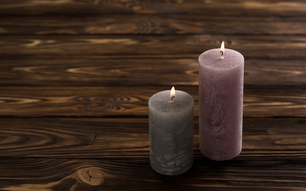 Two decorative candles on brown wooden table