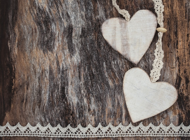 Two decorative hearts on aged wooden background. toned image, valentine day concept.