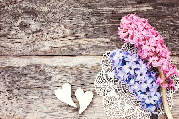 Two decorative hearts and fresh hyacinth on aged wooden background.