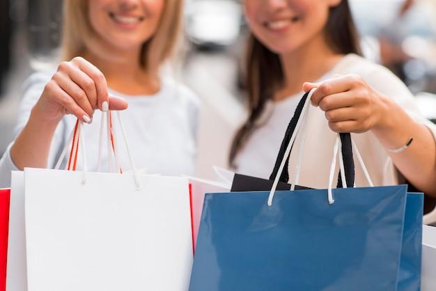 Две расфокусированные женщины, показывающие много сумок после покупок