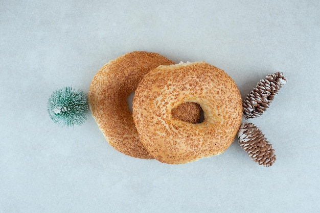 작은 크리스마스 트리와 솔방울 두 맛있는 베이글.