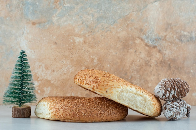 Due deliziosi bagel con piccolo albero di natale e pigne.