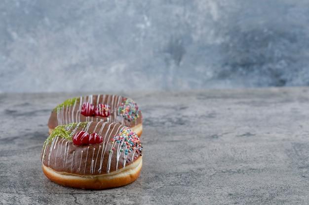 Два восхитительных шоколадных пончика посыпают мраморную поверхность.