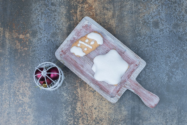 Two delicious christmas cookies on wooden board with red balls on marble background.