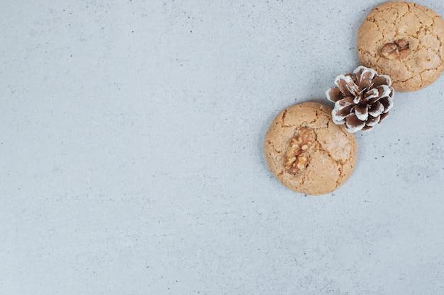 호두와 솔방울을 곁들인 두 개의 맛있는 쿠키