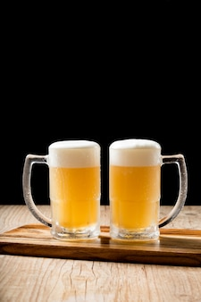 木製のテーブルに2つのおいしいドラフトビールジョッキ