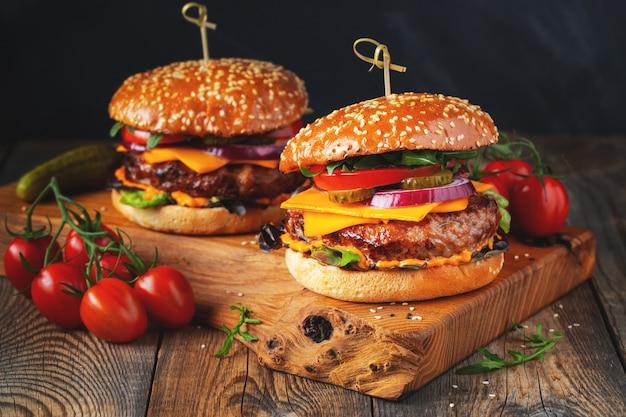 古い木のテーブルに牛肉、チーズ、野菜の 2 つのおいしい自家製ハンバーガー。脂肪の不健康な食べ物のクローズ アップ.