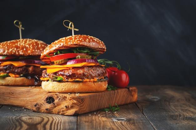 오래 된 나무 테이블에 쇠고기, 치즈, 야채 두 맛있는 수 제 햄버거. 지방 건강에 해로운 ..